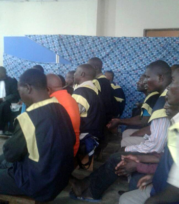 Eighteen men accused of raping 46 young girls sit in a mobile court in Kavumu
