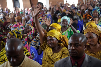 A Congolese woman raises her hand in a service for peace in the Democratic Republic of the Congo