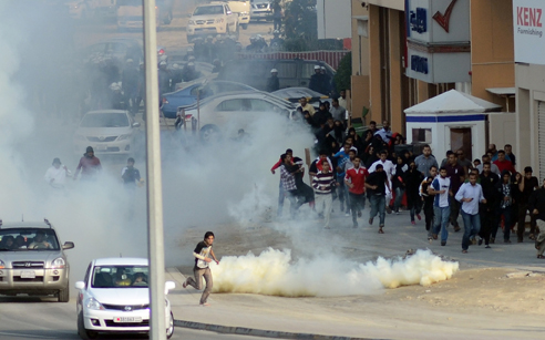 Protestors in Bahrain take cover from tear gas, December 2011