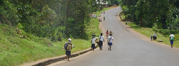 School children walk on a paved road in Kavumu. | PHR Photo